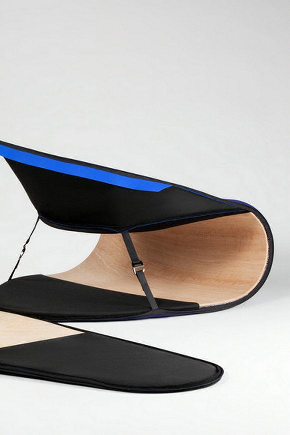 椅子由两块椭圆形胶合板制成,并用带子固定,形成底座和弧形背面。